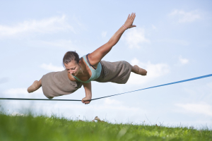 A person balancing with one warm on a taut wire several feet above the ground