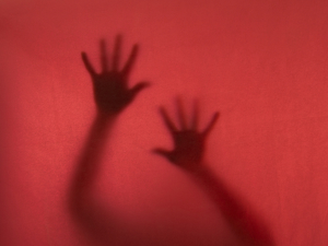 Shadow hands against a red background