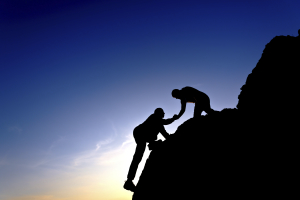 One person helping another person climb up a steep rocky crag